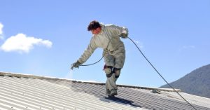 Man applying roof coating with a spray on a metal roof