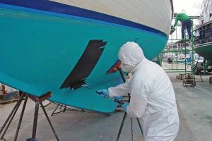 Man applies antifouling coating on boat wearing protective clothing