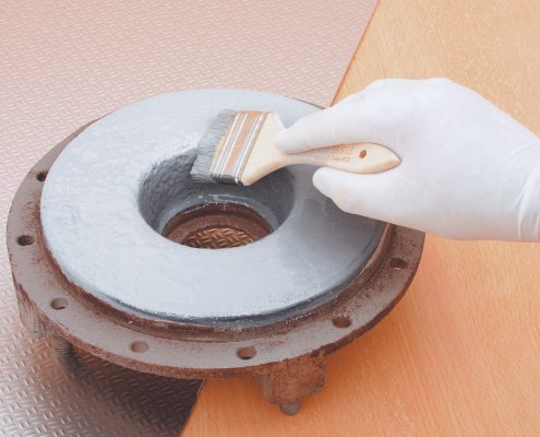 Chemical resistant coatings being applied on a machine part