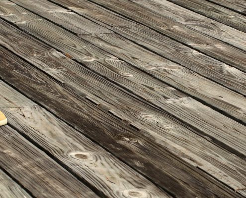 anti slip paint for wood applied on wooden decking in front of a white house