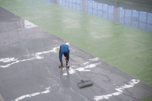 Epoxy concrete paint being applied to flooring