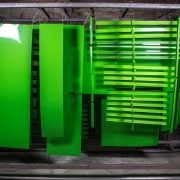 Green powder coated metal objects hanging from the hooks after curing oven.