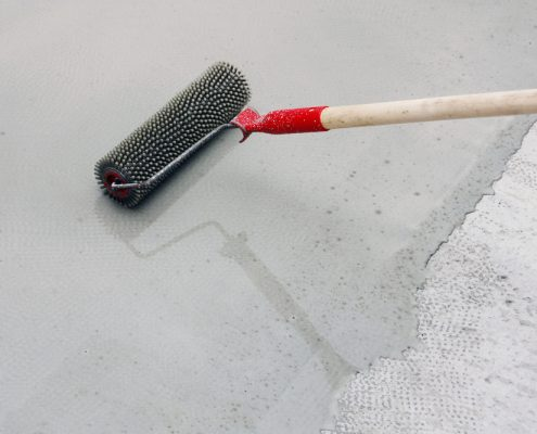 polyaspartic coating being applied on a concrete floor
