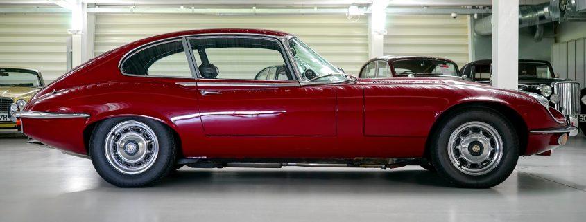 Red car parked in a garage on garage floor paint