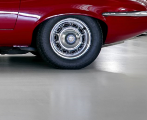 A rear tire of a red car on garage floor coating.