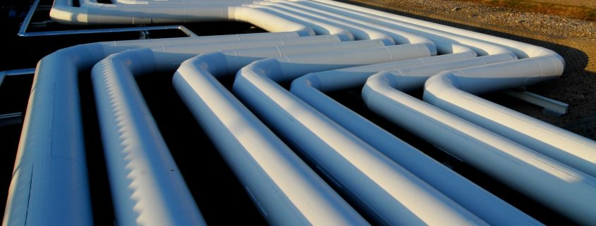 white pipes in a row coated with industrial pipe coating