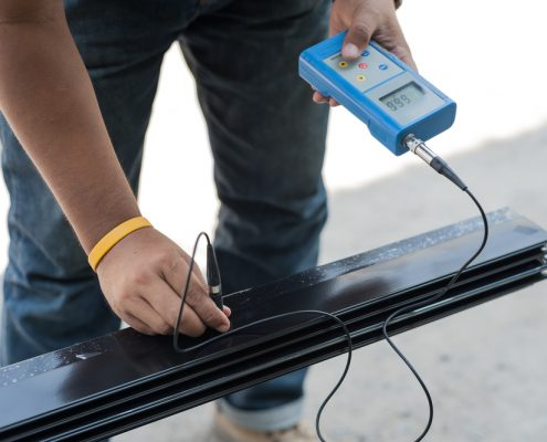 Man measure powder coating thickness with ultrasonic testing