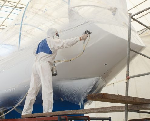 man painting a boat with industrial coating equipment