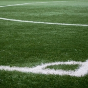 green footbal field with white line marking paint